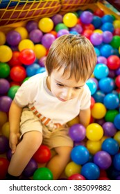 Happy cute child playing and having fun at kindergarten with colorful balls