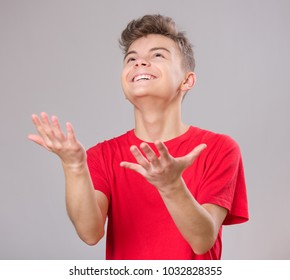 Happy cute child reaching out his palms and catching something. Emotional portrait of caucasian teen boy, smiling. Funny teenager trying to catch something, on gray background.
