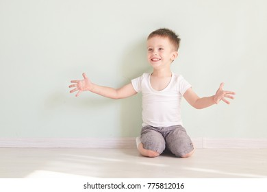 Happy cute child reaching out his palms and catching something.