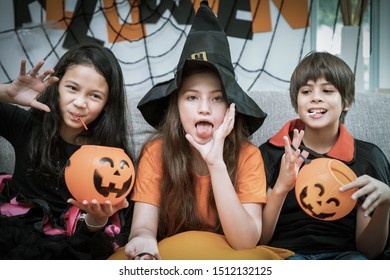 Happy cute children boy and girls in costume on sofa in living room during Halloween party, holding pumpkin Jack-o'-lantern