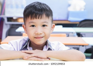 Happy cute chinese schoolboy looking at camera.portrait of asia boy in his classroom.education concept
