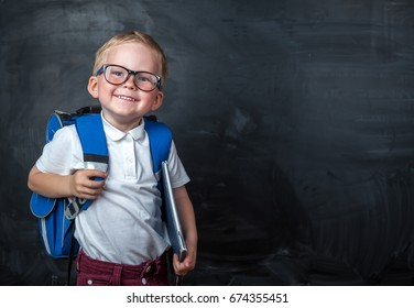Happy cute clever boy in glasses with school bag and book in his hand.  Modern backpack. Child is ready to answer with a blackboard on a background. First time to school. Back to school.
