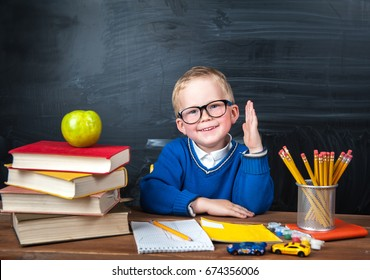 Happy cute clever boy is sitting at a desk in a glasses with raising hand. Child is ready to answer with a blackboard on a background. First time to school. Back to school. Apple and books on desk