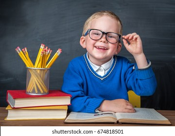 Happy cute clever boy is sitting at a desk in a glasses with raising hand. Child is ready to answer with blackboard ona background. Back to school. Apple and books on desk. First time to school