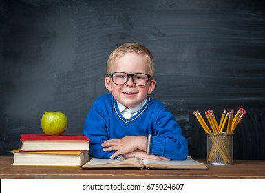 Happy cute clever boy is sitting at a desk in a glasses and smiling. Child is ready to answer with a blackboard on a background. Ready for school. Back to school. Apple and books on desk