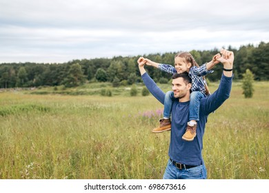 Happy cute daughter piggybacking on her father to see beautiful nature while having stroll together. Handsome young dad and his little child playing on nature. Father showing something to his daughter