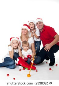 Happy cute family of three children and parents in santa's hats laughing at fireworks isolated on white