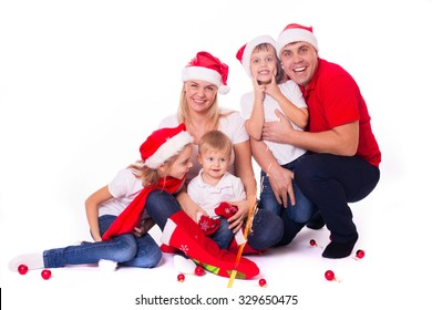 Happy cute family of three children and parents in santa's hats laughing