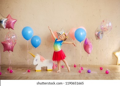 happy cute girl 3-4 years in the rim of a unicorn dancing in a bright outfit, birthday, holiday, balloons