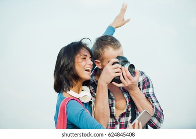 Happy cute girl or beautiful woman taking selfie on smartphone how handsome man, photographer, photographing with camera. Young couple using technology. Summer vacation and travelling