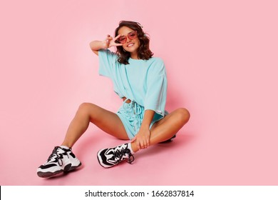 Happy cute  girl listening music by earphones , wearing blue  outfit, stylish trainers sitting on pink background in studio.