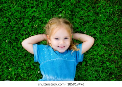 Happy cute girl on green grass in spring park. Healthy lifestyles concept. clover