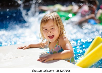 happy cute girl in outdoor swimming pool has fun with splash and toys