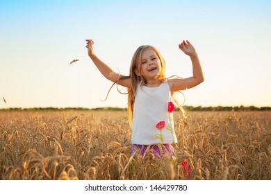 happy cute girl playing in the wheat field on a warm summer day
