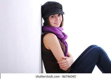 Happy cute girl sitting against wall