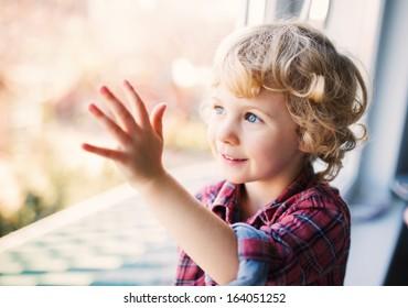 Happy Cute girl sitting alone near window