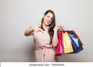 Happy cute girl stands carrying present bags boxes