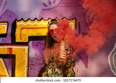 Happy cute girl in sunglasses holds red smoke bomb, standing near the wall with graffiti. Dressed in colorful jacket and cap.