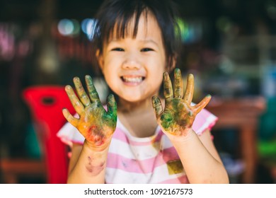 Happy and cute girl uses the hands and fingers for finger painting art work. Picture for concept of school, art subject and play.