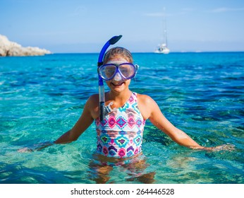 Happy cute girl wearing snorkeling mask ready to dive in the sea