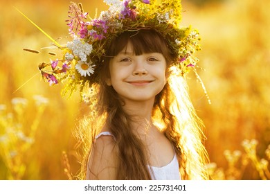 Happy cute girl wearing a wreath of wildflowers