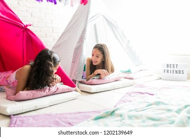 Happy cute girls sharing gossips while resting in tipi tents during pajama party