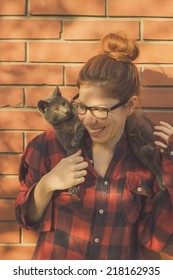 Happy cute hipster girl being silly and playing with her Russian Blue cat
