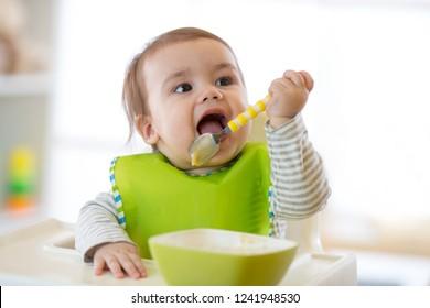 Happy cute Baby Boy Löffel isst sich selbst