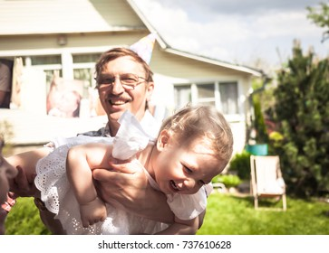 Happy cute laughing baby girl having fun with active senior grandfather outdoors on backyard