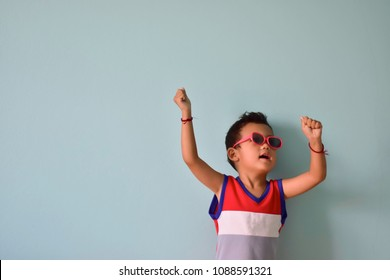 Happy cute little Asian boy in fancy glasses ready to go on vacation, summer break concept with copy space for text