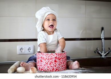 happy cute little baby in a cook cap laughs
