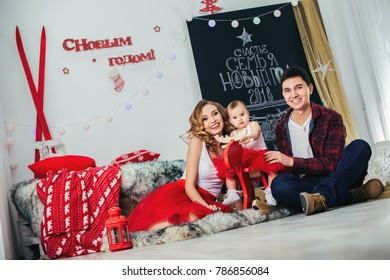 Happy cute little baby girl on rocking dear at Christmas tree with a toy, dressed in red dress New Year room at home. Child good mood. Lifestyle, family and holiday concept. With parents