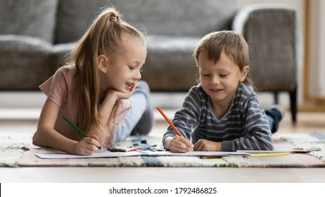 Happy cute little blonde girl lying on floor carpet with smiling funny preschool brother, enjoying drawing pictures with colorful pencils in paper albums indoors, kids weekend pastime at home.