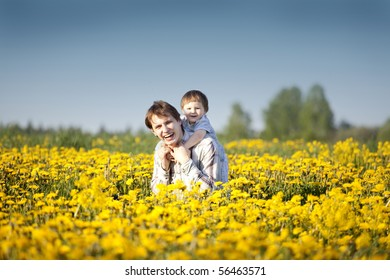 happy cute little boy having fun with his dad in the field of dandelions