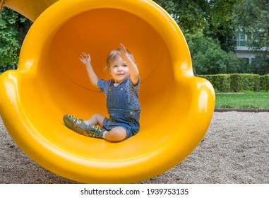 Happy cute little child boy having fun on a yellow slide outdoor in the park, sunny summer day in children playground
