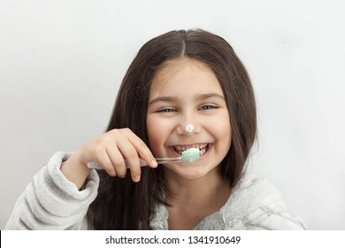 Happy cute little child girl brushing her teeth on light background. Space for text. Healthy teeth.