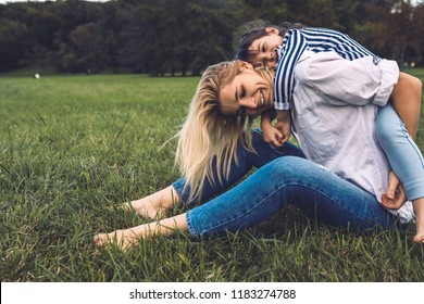 Happy cute little daughter on a piggy back ride with her mother. Loving smiling woman and her little girl sitting on green grass in the park. Mom and kid have fun outside. Good relationship.Motherhood