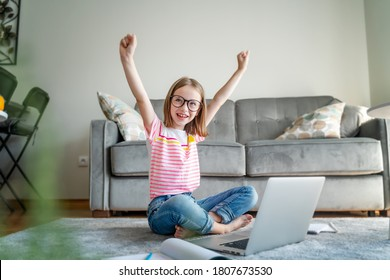 Happy cute little girl 8 years old in a striped t-shirt and jeans with glasses sits at home on a carpet in front of a laptop, remote education technologies and homework