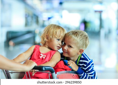 Happy cute little girl and boy at airport riding on luggage cart
