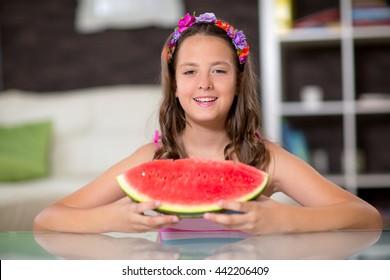 Happy cute little girl eating watermelon