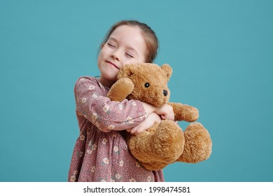 Happy cute little girl embracing her fluffy brown teddybear