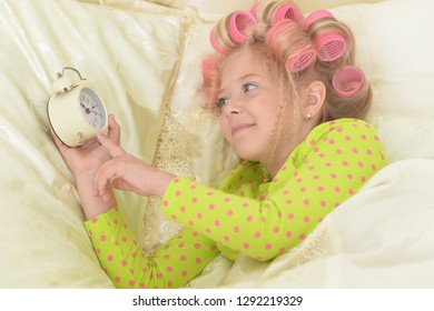 Happy cute little girl in hair curlers awaked