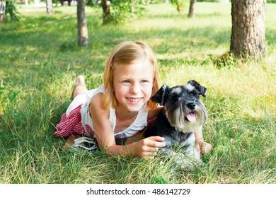 Happy cute little girl hugging her little dog
