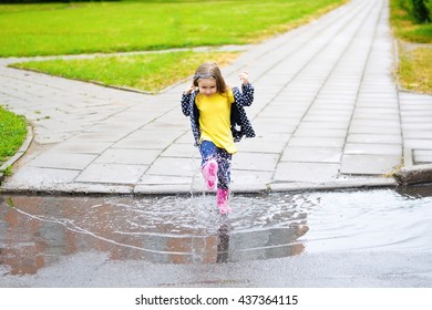 Happy cute little girl jumping in puddle after rain in summer