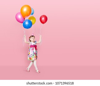 Happy cute little girl  with multi-coloured balloons  on a pink background. mother's day, birthday