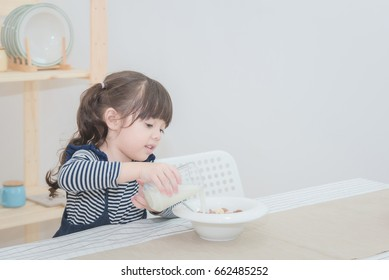 Happy cute little girl prepare healthy breakfast in the morning. Photo series of family, kids and happy people concept.
