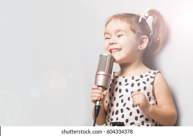 Happy Cute little girl singing a song on microphone.