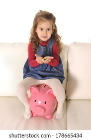 Happy Cute little girl sitting on huge piggy bank holding euro Coins
