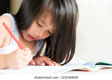 Happy cute little girl smiling and holding red pencil and drawing, writing on a book to do homework.