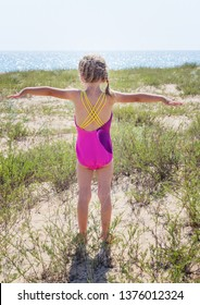Happy cute little girl standing on beach. Holiday on ocean coast for family with children. Child play at the sea.